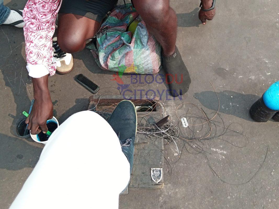 Les cireurs sont munis d'un sac au dos, d'une brosse à cirage en main et d'un morceau de bois servant de pose-pieds.